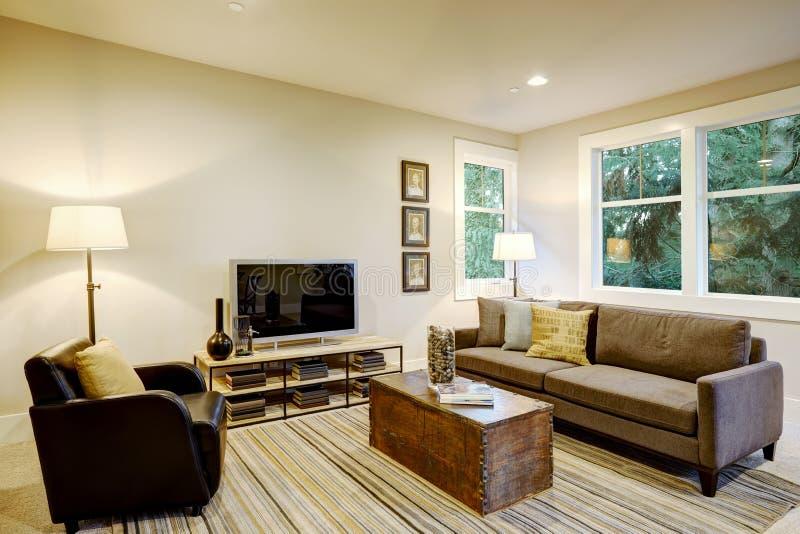 与灰色沙发和树干咖啡桌的家庭娱乐室内部 库存图片