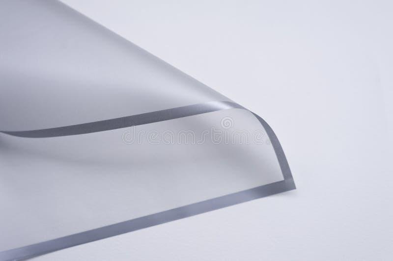 与灰色边缘的透明纸角落在白色背景 免版税库存照片