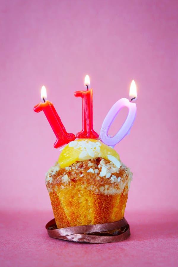 与灼烧的生日蜡烛的松饼作为第一百和十 免版税库存照片