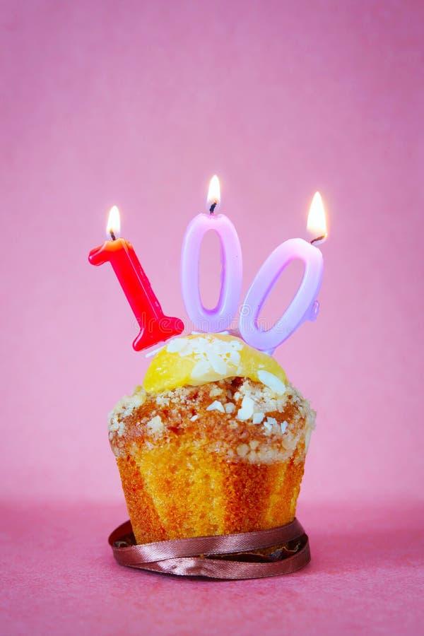 与灼烧的生日蜡烛的松饼作为第一百 免版税库存图片