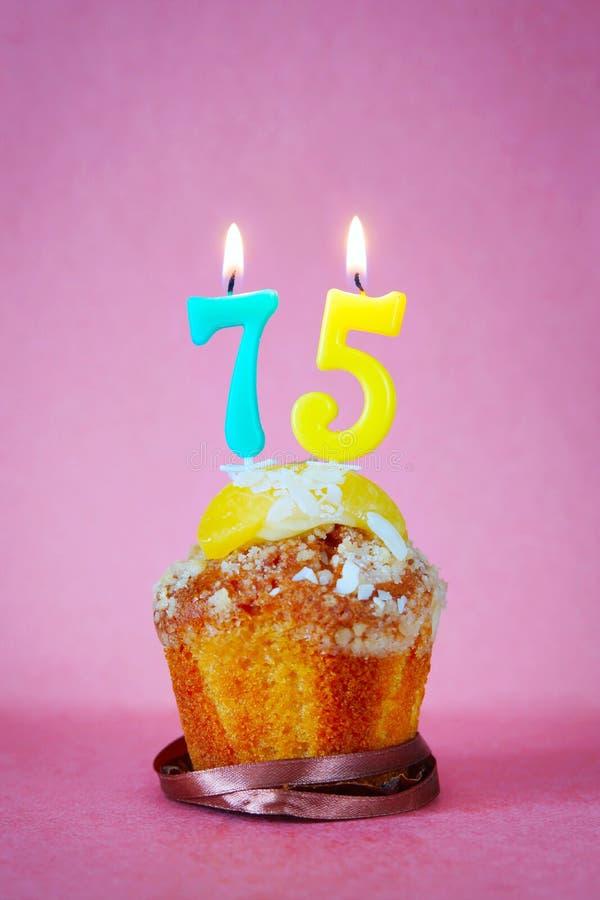 与灼烧的生日蜡烛的松饼作为第七十五 免版税库存照片