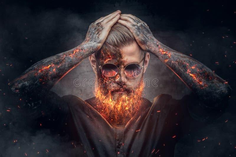与灼烧的胡子和胳膊的恶魔般的男性 免版税库存图片