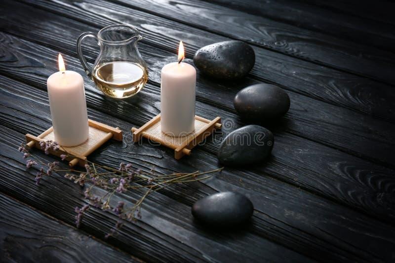 与灼烧的蜡烛和温泉石头的美好的构成在黑暗的木桌上 库存图片