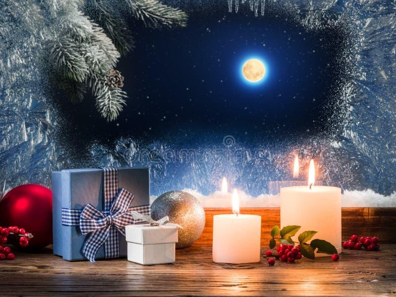 与灼烧的蜡烛的圣诞节礼物在与pa的窗台 图库摄影