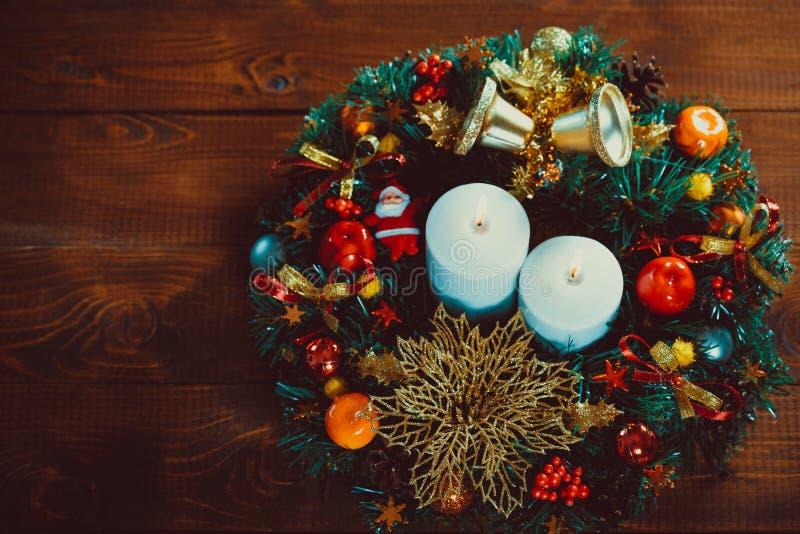 与灼烧的蜡烛的圣诞节花圈在木桌上 库存照片