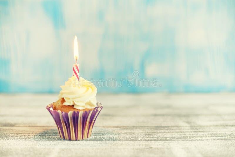 与灼烧的蜡烛的欢乐杯形蛋糕 免版税库存照片