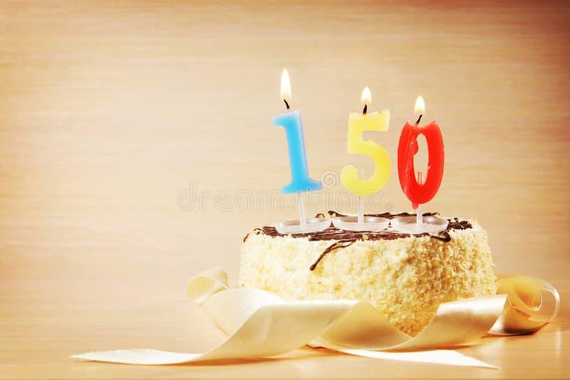 与灼烧的蜡烛的生日蛋糕作为第一百和五十 库存图片