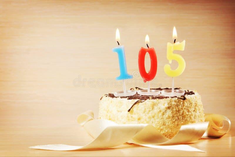 与灼烧的蜡烛的生日蛋糕作为第一百和五 免版税库存图片
