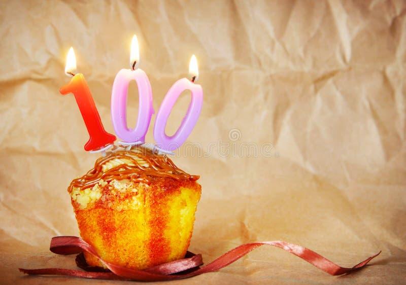 与灼烧的蜡烛的生日蛋糕作为第一百 库存照片