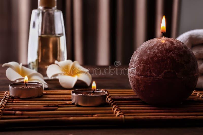 与灼烧的蜡烛的美好的温泉构成在木桌上 库存图片