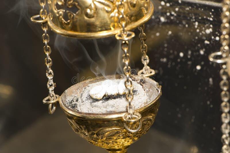 与灼烧的香火的黄铜香炉仪式香炉在它 库存照片