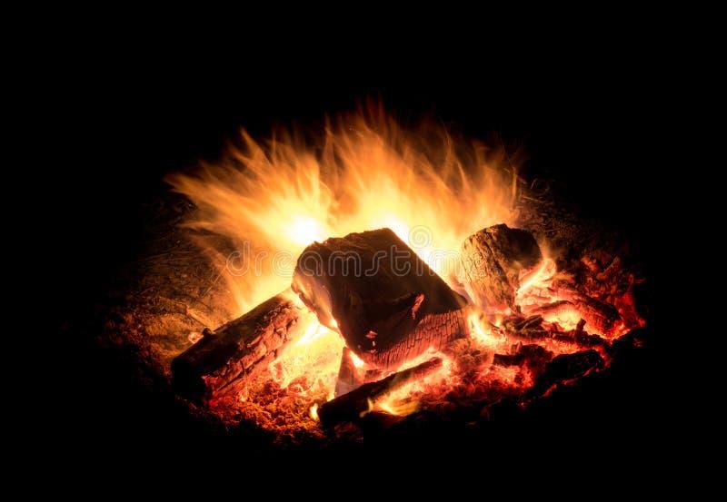 与炭烬的灼烧的火在黑背景前面 免版税图库摄影