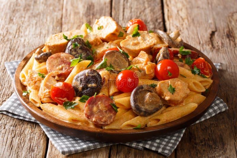 与炸鸡、狂放的蘑菇、熏制的香肠、蕃茄和乳脂状的乳酪调味料特写镜头的热的辣penne面团在板材  库存照片