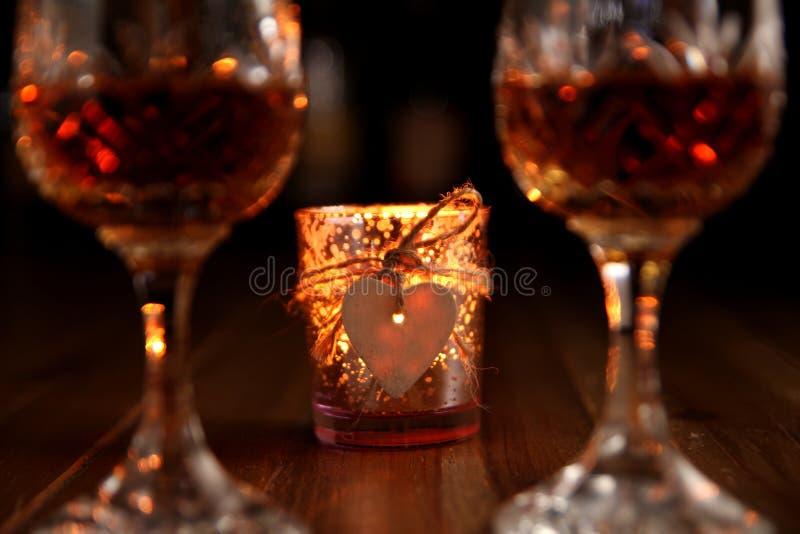 与点蜡烛的心脏的情人节浪漫饮料 免版税图库摄影