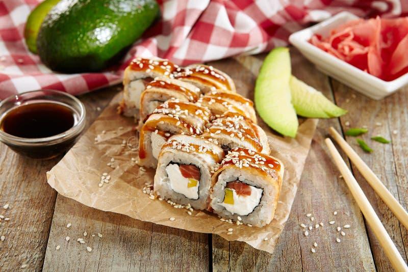 与烂醉如泥的Daikon的三文鱼和熏制的鳗鱼寿司卷 免版税库存图片