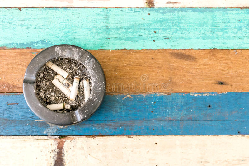 与烟灰缸的香烟在木桌上 库存图片