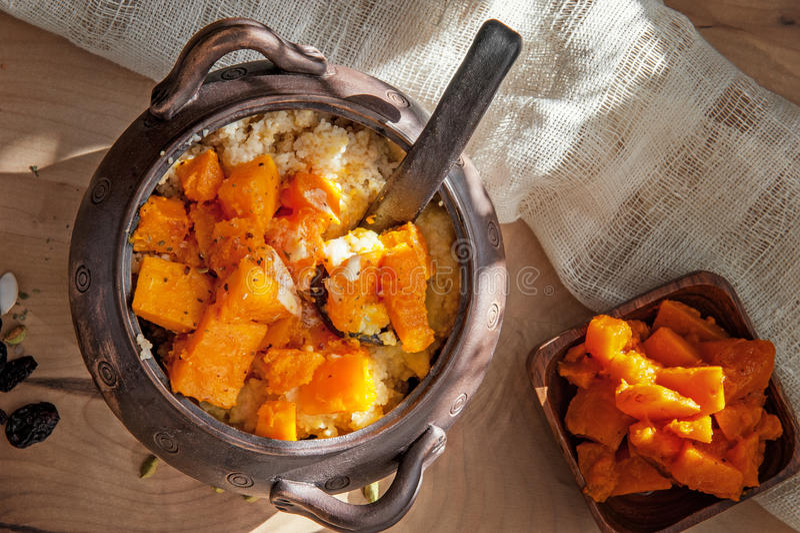 与烤南瓜大大块的素食麦子粥在一个泥罐的在土气样式有机食品 库存图片