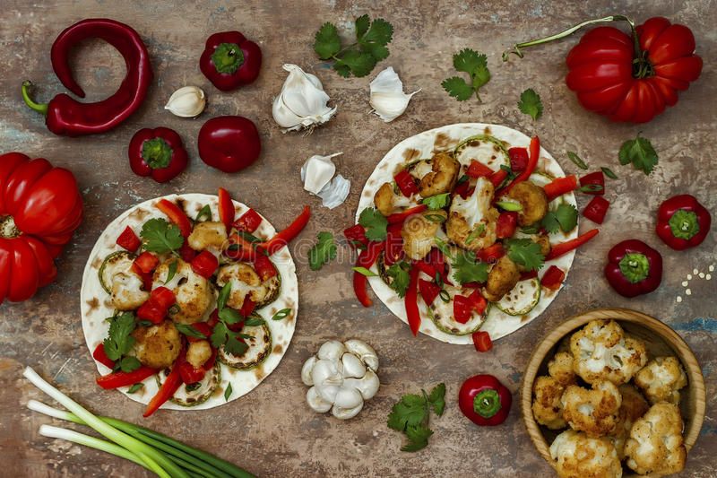与烤花椰菜、夏南瓜和蕃茄辣调味汁的辣素食者炸玉米饼在土气木切板 免版税库存图片