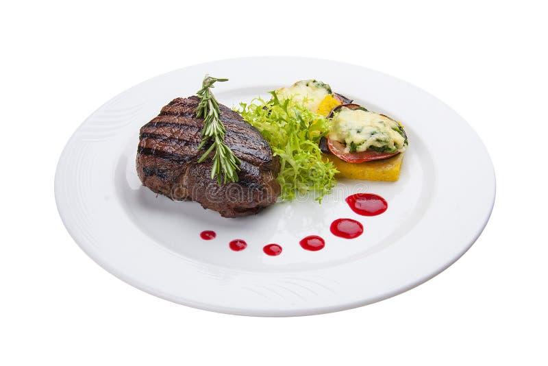 与烤菜和煎蛋卷的牛排 在一块白色板材上 免版税库存照片