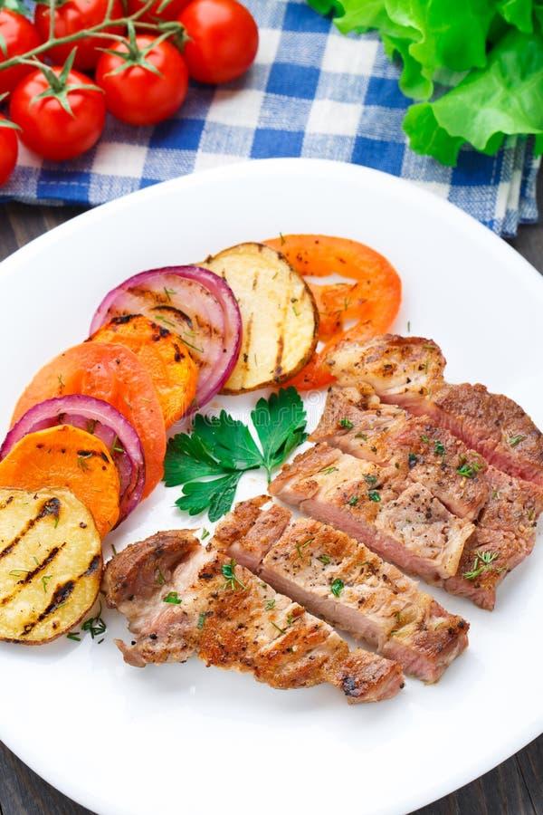 与烤菜的牛排在板材 免版税库存图片