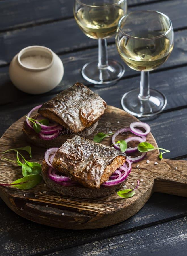 与烤鱼的三明治和快的烂醉如泥的葱和两杯白葡萄酒 免版税图库摄影