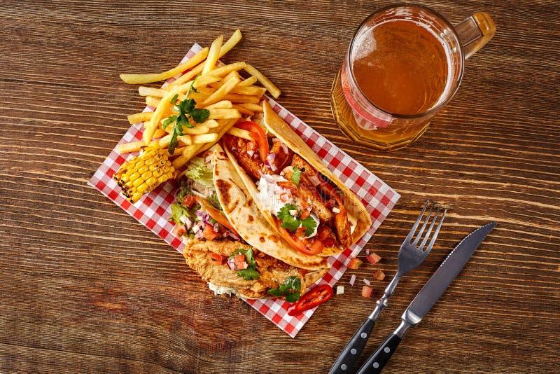 与烤鸡内圆角的第一个玉米粉薄烙饼,第二与鱼片,调味汁和啤酒在木桌上 顶视图 库存照片