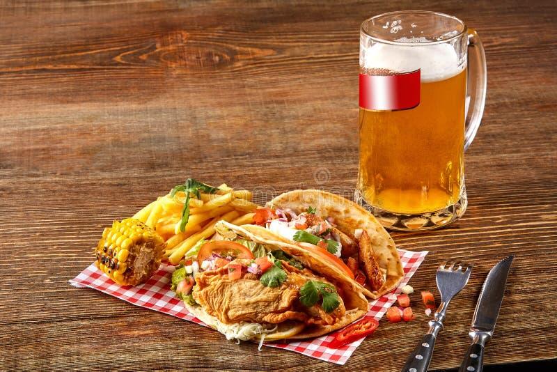 与烤鸡内圆角的第一个玉米粉薄烙饼,第二与鱼片,调味汁和啤酒在木桌上 库存照片