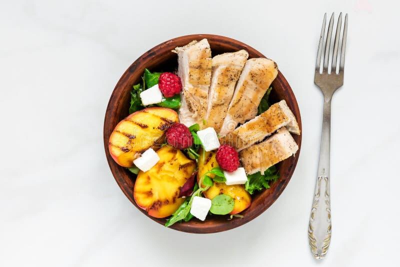 与烤鸡的夏天沙拉和桃子、希腊白软干酪和莓在一个碗有叉子的 健康的食物 免版税库存照片