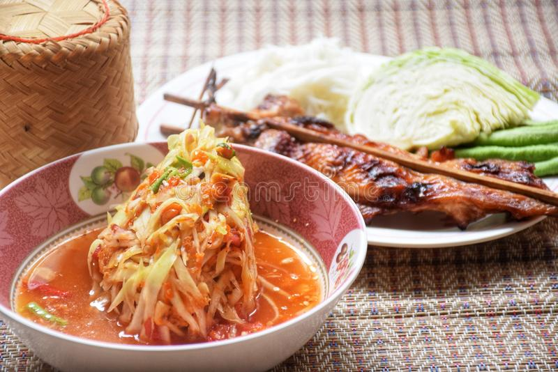 与烤鸡的绿色番木瓜沙拉在原始的泰国席子 免版税图库摄影