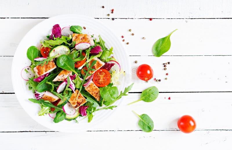 与烤鸡胸脯-蕃茄、黄瓜、萝卜和混合莴苣叶子的新鲜蔬菜沙拉 图库摄影