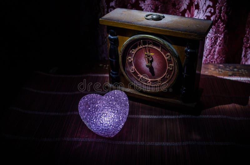 与烧在黑暗的背景的甜点的情人节构成多彩多姿的心脏和老葡萄酒时钟、时间和爱概念, 库存照片