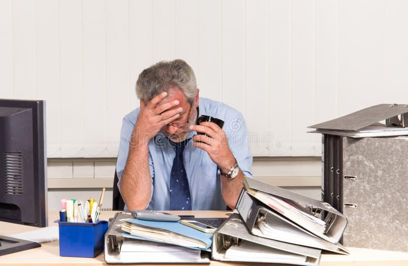 与烧坏的商人过度紧张在他的办公桌 库存照片