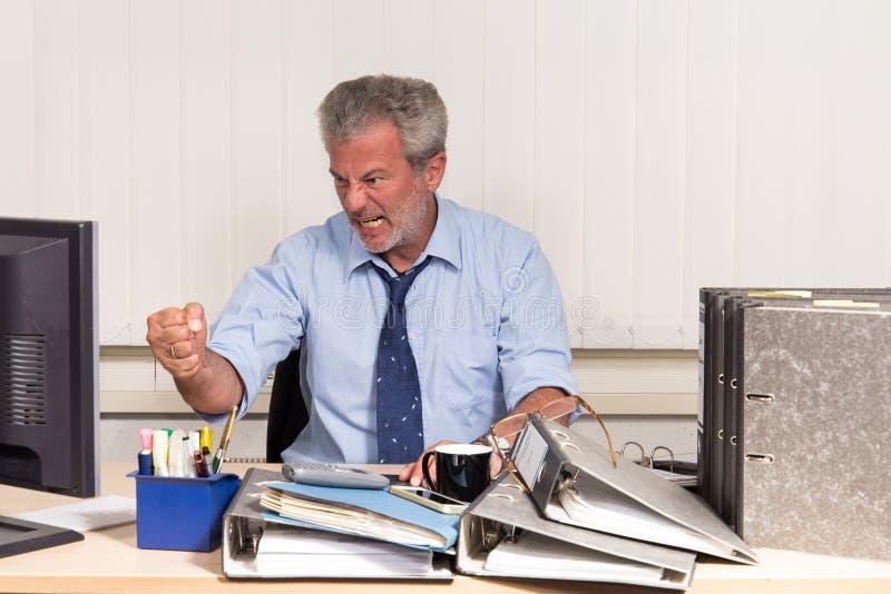 与烧坏的商人过度紧张在他的办公桌 库存图片