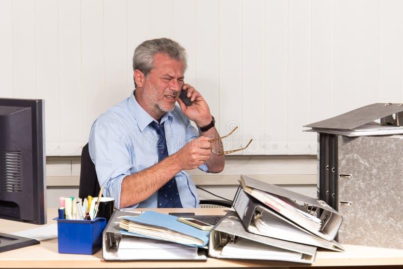 与烧坏的商人过度紧张在他的办公桌 免版税图库摄影
