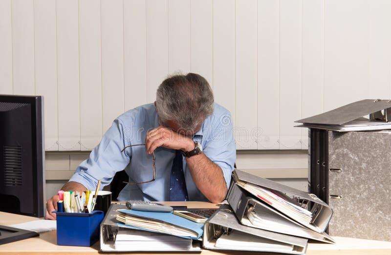 与烧坏的商人过度紧张在他的办公桌 免版税库存照片