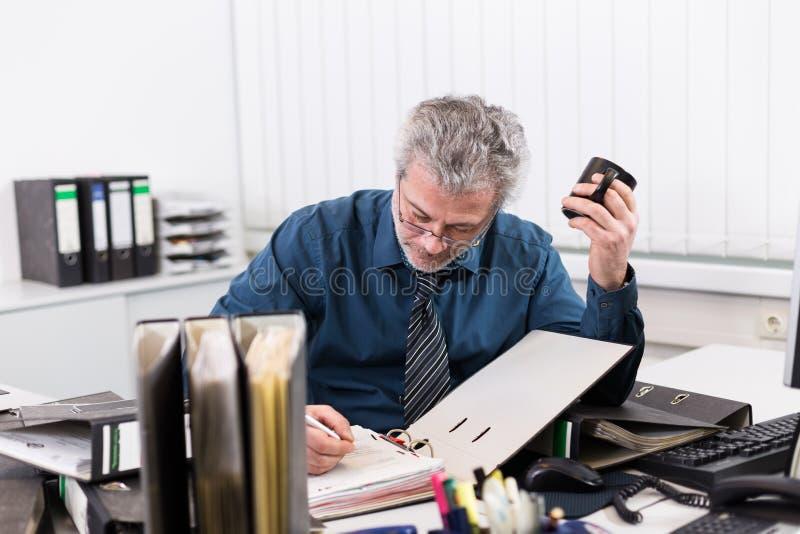 与烧坏的商人过度紧张在他的办公桌 图库摄影