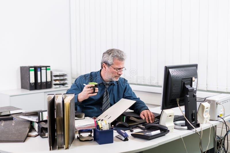 与烧坏的商人过度紧张在他的办公桌 免版税库存图片