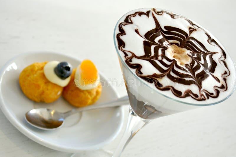与热奶咖啡和甜点的意大利早餐 免版税图库摄影