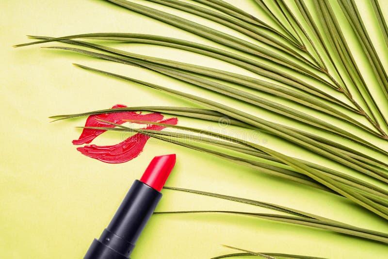 与热带叶子的红色口红和嘴唇印刷品在绿色背景 免版税库存图片