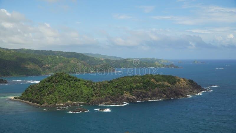 与热带海岛、海滩、岩石和波浪的海景 卡坦端内斯省,菲律宾 图库摄影