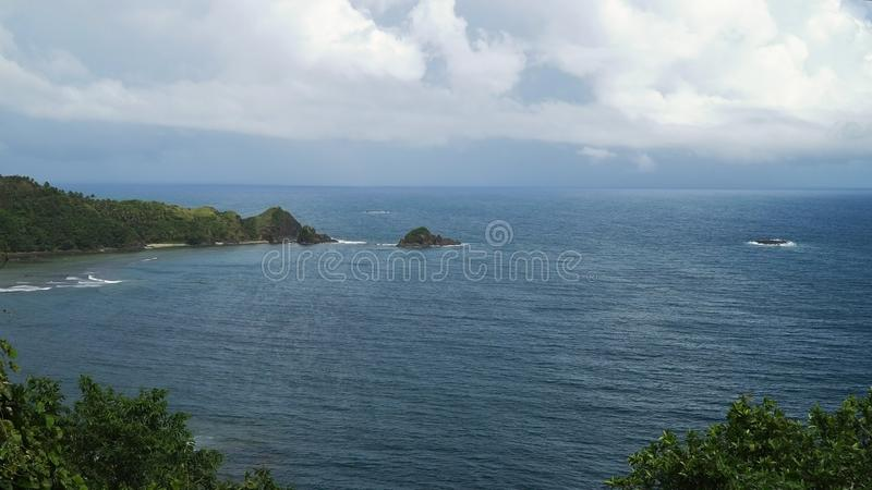 与热带海岛、海滩、岩石和波浪的海景 卡坦端内斯省,菲律宾 库存照片