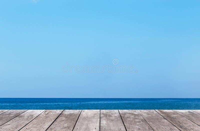与热带蓝色海和蓝天的老木阳台大阳台地板 图库摄影