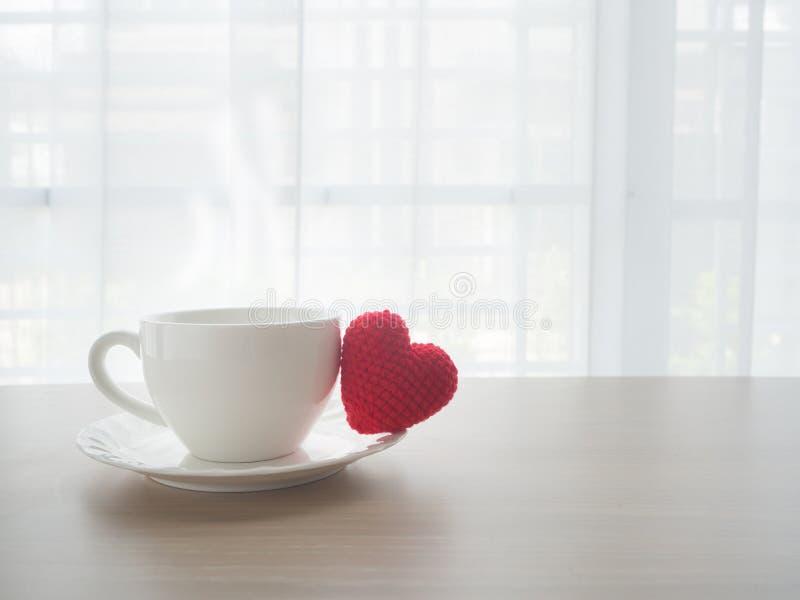 与热的咖啡杯的木办公室桌和红色心脏塑造标志 免版税库存照片