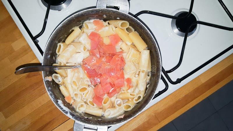 与烹调在一个大平底深锅平底锅的三文鱼的面团在厨房里 免版税库存图片