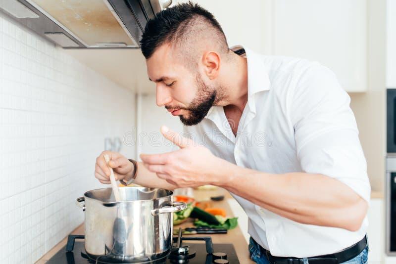 与烹调汤和准备晚餐的人的现代生活方式 准备食物的大厨 免版税库存照片