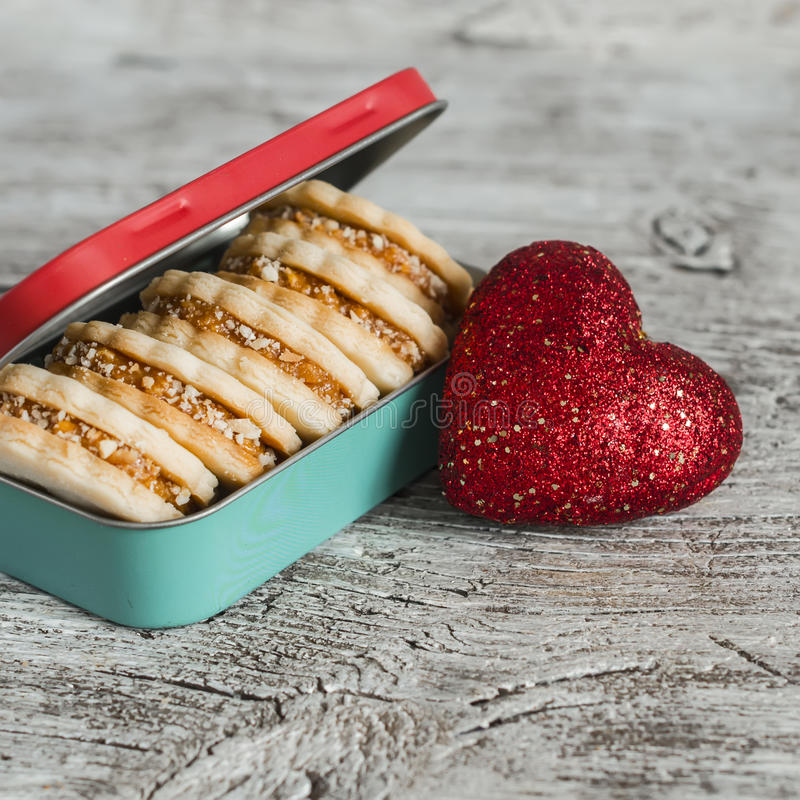 Download 与焦糖奶油和核桃在葡萄酒金属箱子,明亮的木表面上的装饰红色心脏的曲奇饼 库存照片 - 图片 包括有 礼品, 点心: 62527864