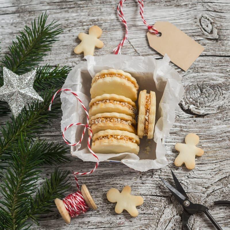 与焦糖奶油和核桃的饼干 自创圣诞节礼物,轻的木表面上 免版税库存图片