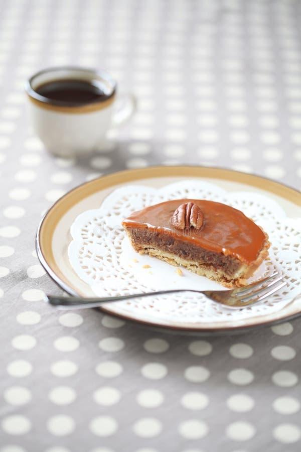 与焦糖顶部的微型山核桃饼在有一杯咖啡的一块板材 免版税库存照片