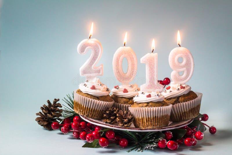 与照明设备蜡烛的新年快乐2019杯形蛋糕 库存照片图片