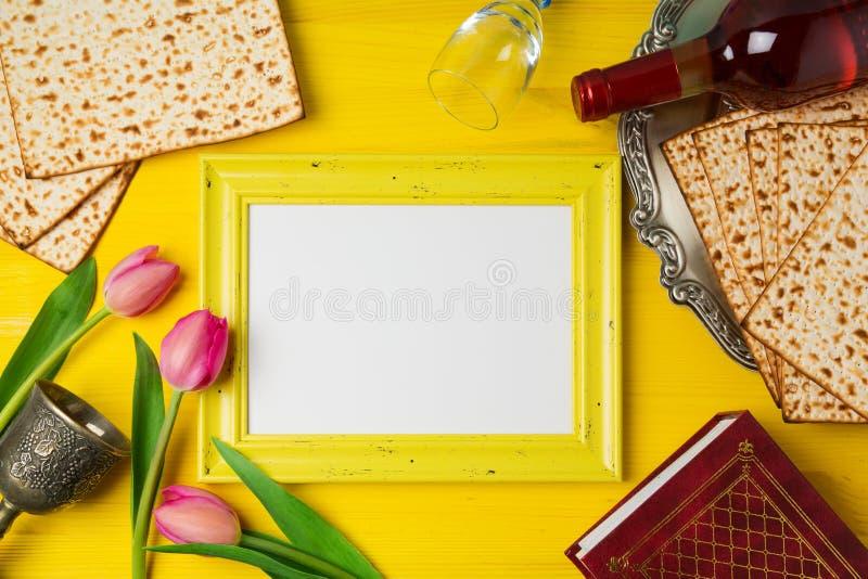 与照片框架、发酵的硬面和酒瓶的犹太假日逾越节Pesah庆祝在黄色木背景 免版税库存图片